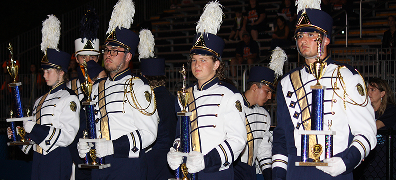 Members of the Midlothian High School Marching Trojans holding trophies